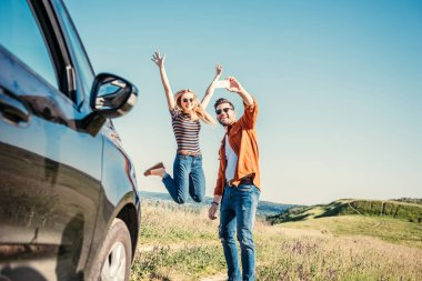 happy young woman jumping with wide arms while her boyfriend taking selfie on smartphone near car in field