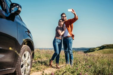 stylish man taking selfie with girlfriend near car on rural meadow