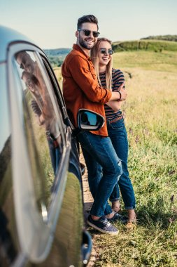 stylish smiling couple in sunglasses standing near car on rural meadow