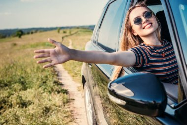 Stylish woman in sunglasses leaning out hand from car window stock vector