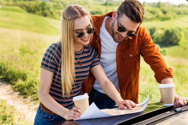smiling stylish couple of tourists with paper cups of coffee looking for destination on map near car in rural field