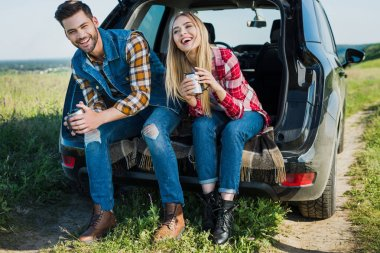 smiling couple of stylish tourists with coffee cups sitting on car trunk in rural field