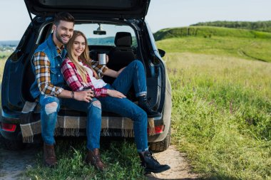 smiling couple with coffee cups sitting on car trunk in rural field