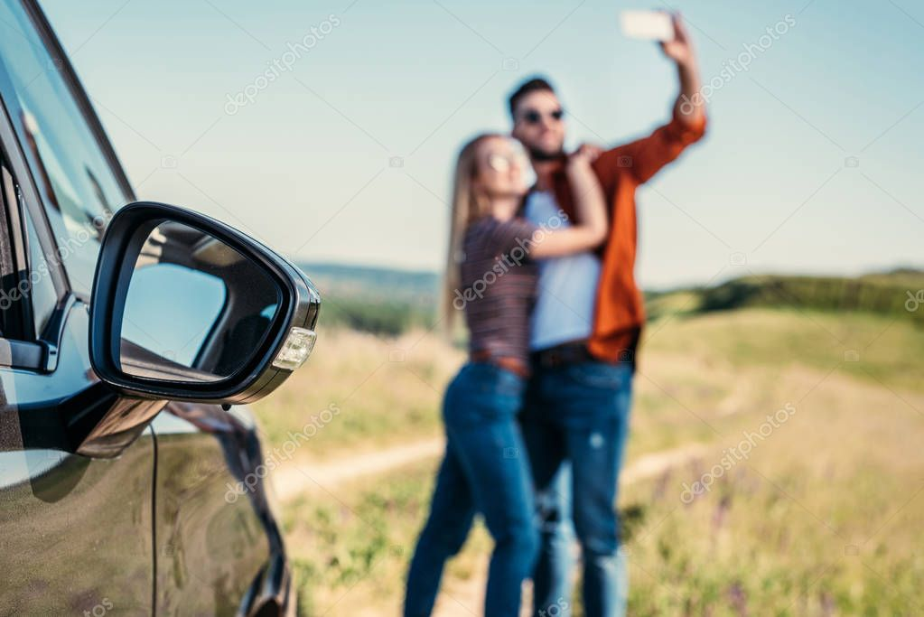 close up view of side mirror of car and couple taking selfie on blurred background