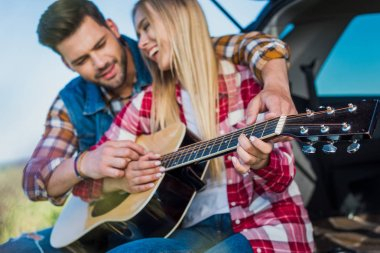 smiling man teaching smiling girlfriend to play on acoustic guitar on car trunk