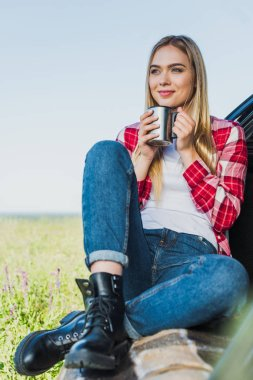attractive young woman sitting on car trunk with coffee cup in rural field
