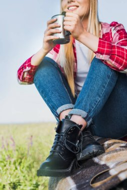 cropped image of young woman sitting on car trunk with coffee cup in rural field