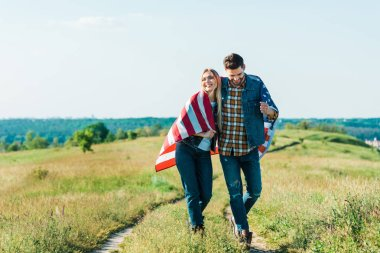 happy young couple with american flag on rural meadow, independence day concept