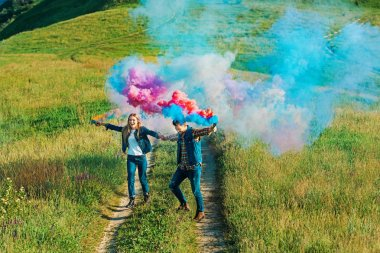 high angle view of couple holding colorful smoke bombs on rural meadow