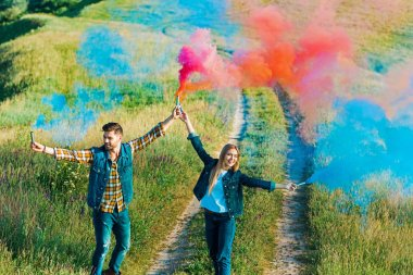 high angle view of young couple holding colorful smoke bombs on rural meadow