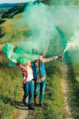 elevated view of young couple holding green smoke bombs in field