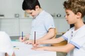 boční pohled na malé bratry kreslení obrázků u stolu doma