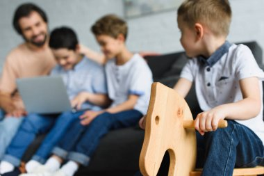 selective focus of little boy on wooden horse toy and family using laptop together on sofa at home