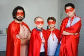 Photo portrait of father and little sons in red superhero costumes with arms crossed at home