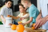 Fotografie Teilansicht der Familie frischen gepressten Orangensaft in Küche zu Hause