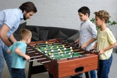 Photo side view of father and little sons playing table football together at home