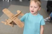 Ritratto di bambino sveglio con il giocattolo in legno piano in mano a casa