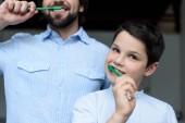 Fotografie částečný pohled otce a syna čistit zuby dohromady doma