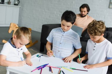kids drawing pictures with colorful pencils while father using laptop on sofa at home