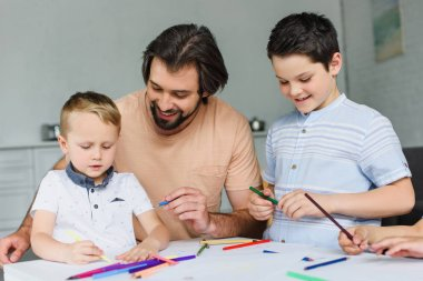 Portrait of father helping sons draw pictures with colorful pencils at home stock vector