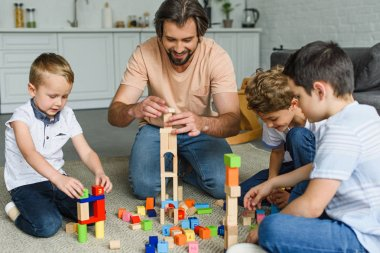 cheerful father and kids playing with wooden blocks together on floor at home
