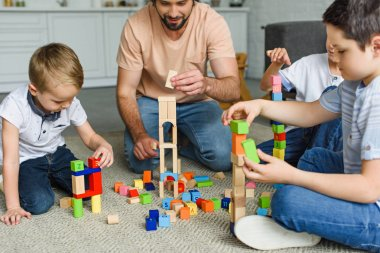 partial view of father and kids playing with wooden blocks together on floor at home