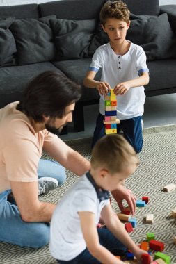 side view of father and kids playing with wooden blocks together on floor at home