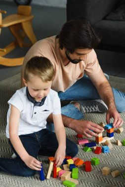 focused father and son playing with wooden blocks together at home