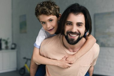 portrait of happy father and little son piggybacking together at home