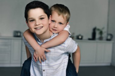 portrait of happy brothers piggybacking together at home