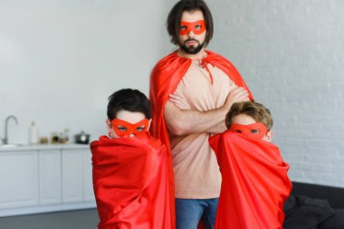 portrait of man and sons in red superhero costumes looking at camera at home