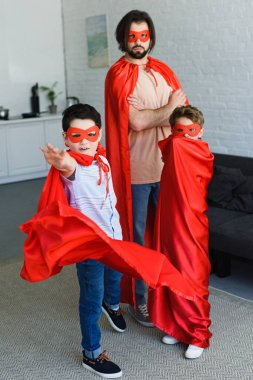 man and cute little sons in red superhero costumes at home