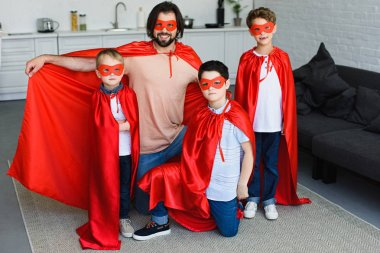smiling father and little sons in red superhero costumes at home