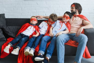 smiling father sitting near sleeping sons in red superhero costumes on sofa at home