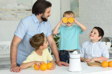 family making fresh orange juice in kitchen at home