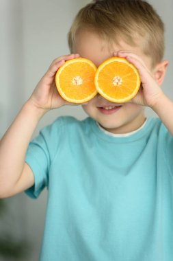 obscured view of little boy covering eyes with pieces of fresh orange in hands