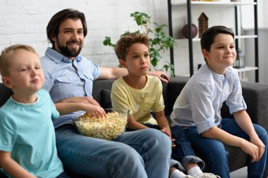 smiling man and little sons with popcorn watching film together at home
