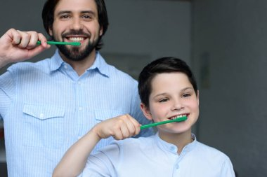portrait of father and son brushing teeth together at home