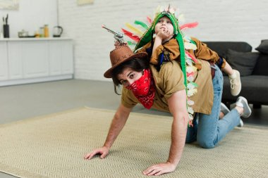 father and little son in costumes playing together at home