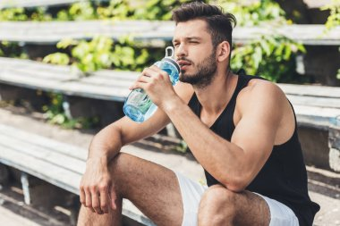 sportsman drinking water and sitting on bench at sport playground