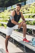 Fotografie junge Sportler in Ohrhörer mit Smartphone in laufenden Armbinde-Kasten Übung auf Bank am Spielplatz sport