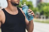 Fotografie oříznutý snímek mladého sportovce pitné vody z láhve