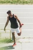 Fotografia giovane atleta maschio che si estende vicino alla pista di atletica al campo da giuoco di sport