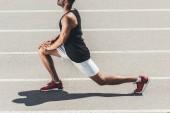 Fotografia immagine potata del pareggiatore maschio che allunga sulla pista di atletica al campo da giuoco di sport