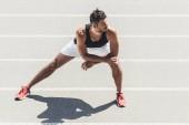 Pareggiatore maschio giovane che allunga sulla pista di atletica al campo da giuoco di sport