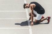 mladý sportovec na nízký start na Běžecká stopa
