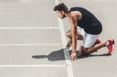 boční pohled mladé mužské sportovce na nízký start na Běžecká stopa