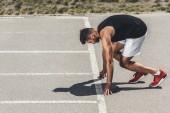 Fotografia atleta maschio giovane serio su basso start sulla pista di atletica