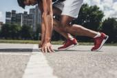částečný pohled muž sprinter do výchozí pozice na Běžecká stopa