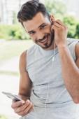 Detailní portrét šťastný mladý muž poslouchá hudbu s smartphone a sluchátka a při pohledu na fotoaparát venku